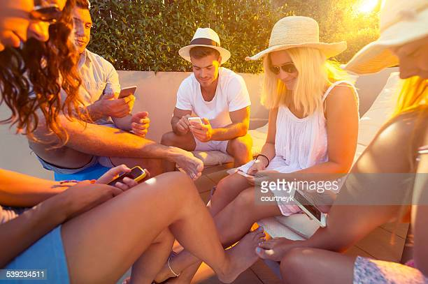 Group of friends using mobile phones.