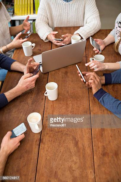Group of friends using smartphones in a cafeteria