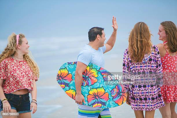 Group of friends (16-17) walking on beach