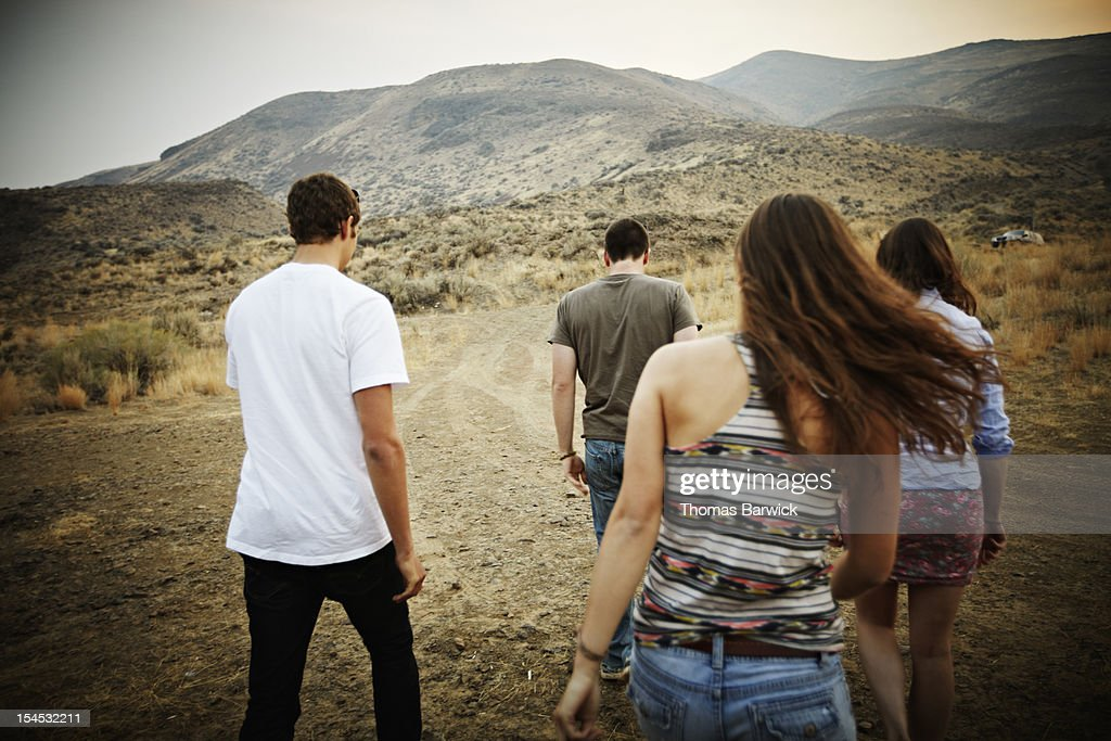 Group of friends walking on dirt road at sunset : Stock Photo