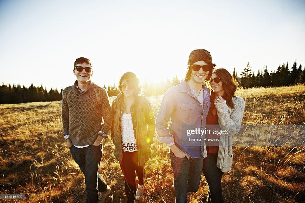 Group of friends walking through field at sunset : Stock Photo
