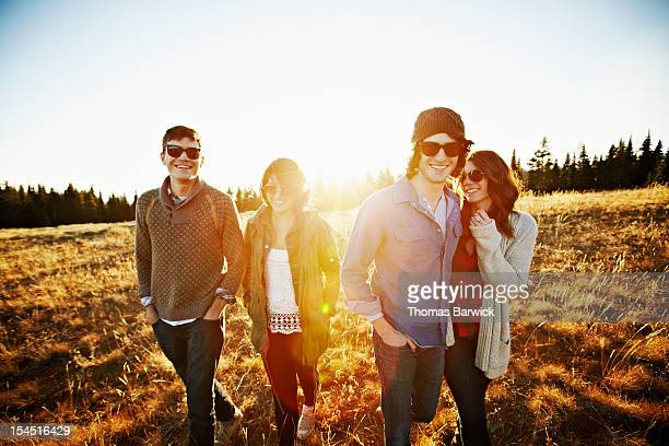 Group of friends walking through field at sunset