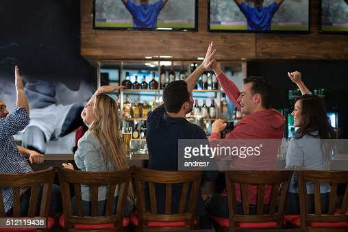 Group of friends watching a football game at the pub