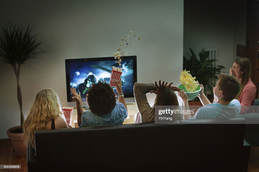 Group of Friends Watching Halloween Scary Movie Together at Home