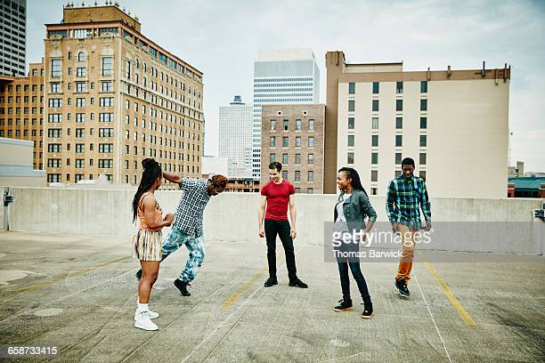 Group of friends watching man dance on rooftop