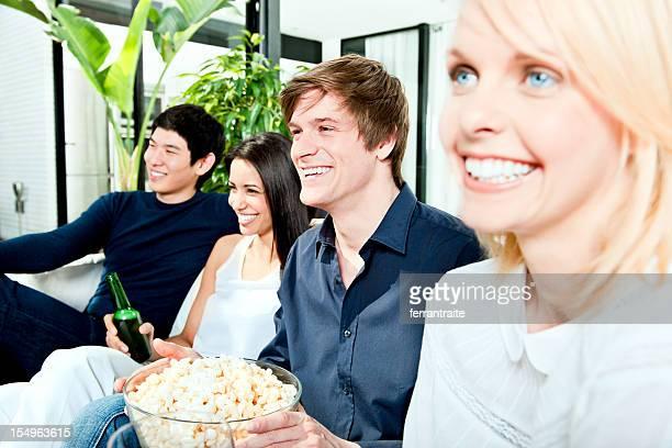 Groupe d'amis en regardant la télévision et rire