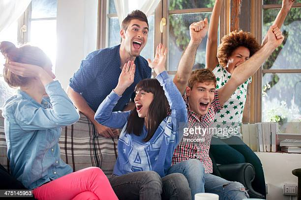 Group of friends watching tv cheering
