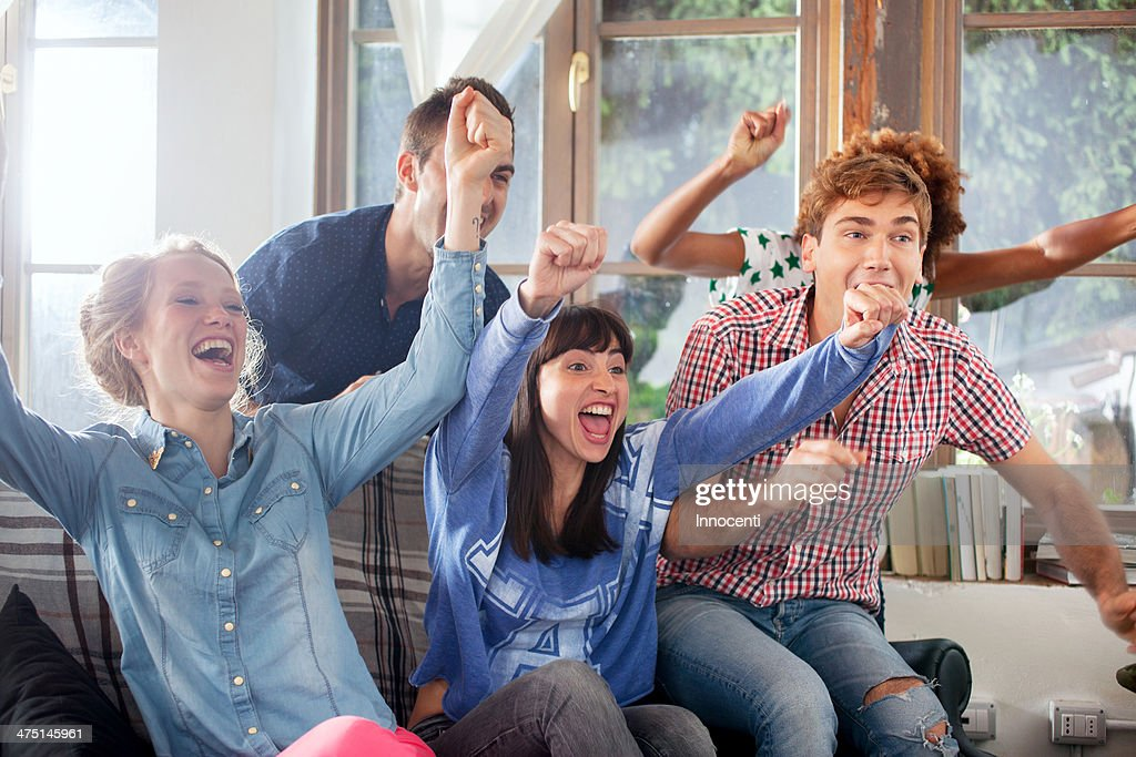 Group of friends watching tv cheering : Stock Photo