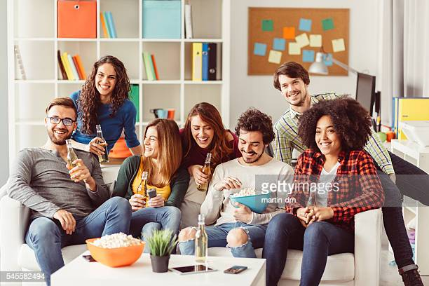 Group of friends watching tv in the office