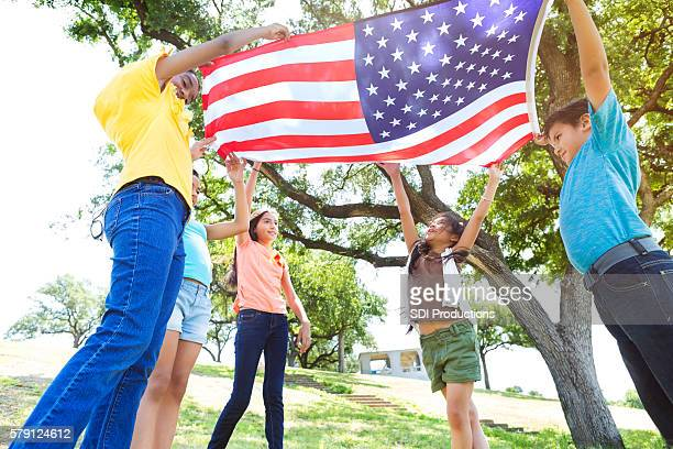 Group of friends wave American flag