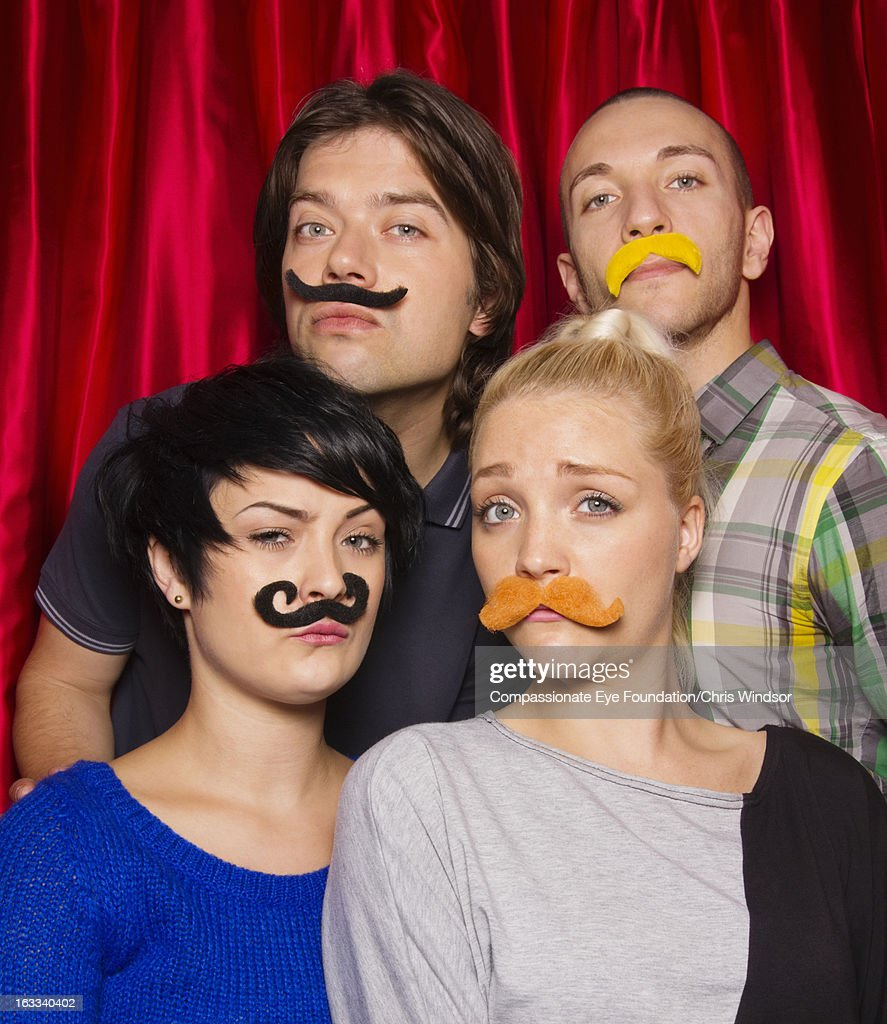 Group of friends wearing moustaches in photo booth : Stock Photo