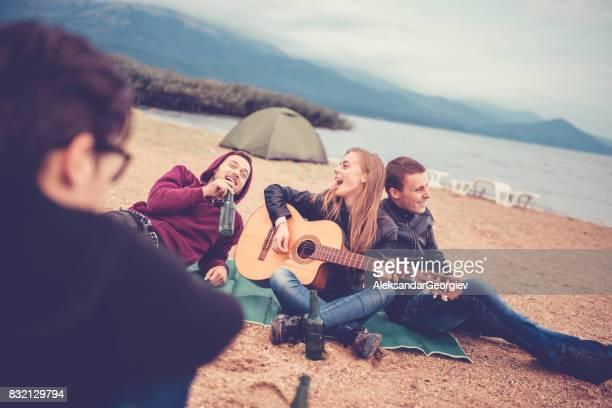 Groupe d'amis avec guitare acoustique boire de bière sur la plage