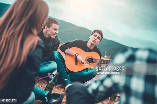 Group of Friends with Acoustic Guitar Singing at Beach Party