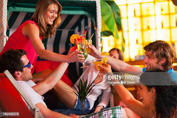 Group of friends with cocktails at indoor beach party
