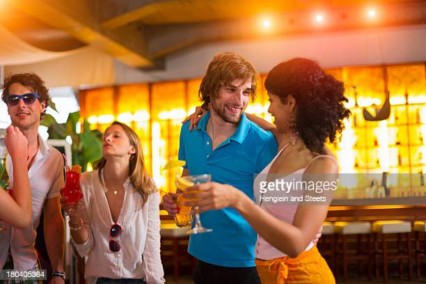 Group of friends with cocktails in bar