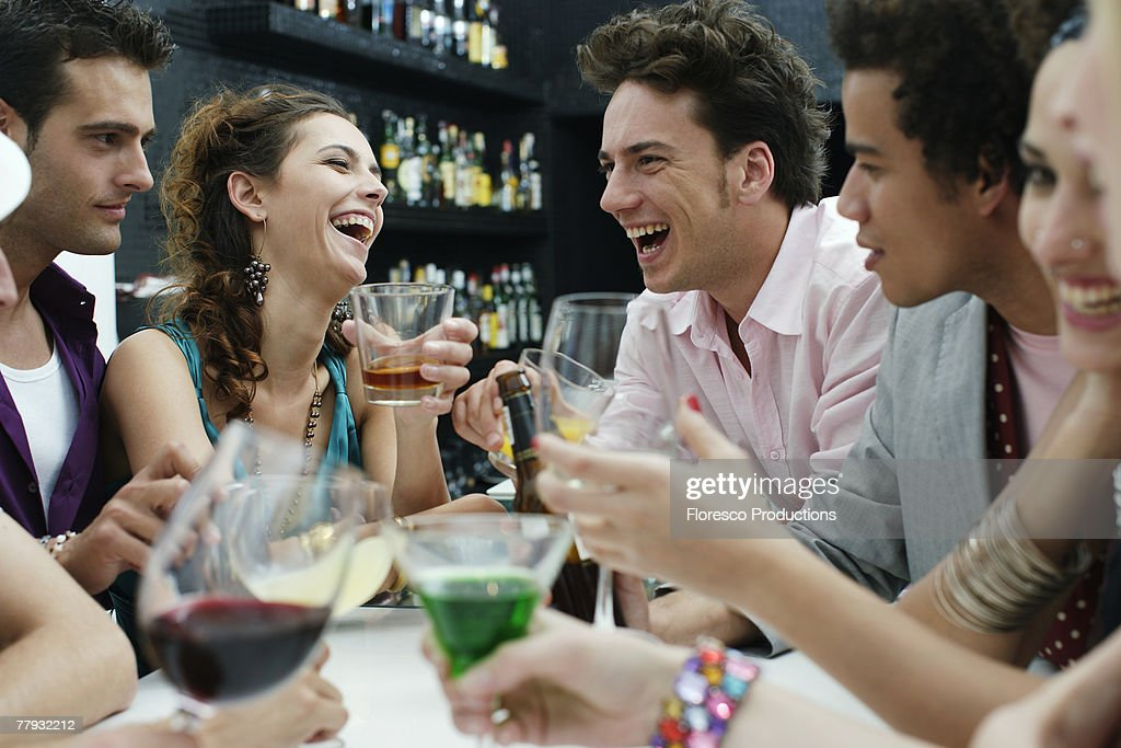 Group of friends with drinks having fun