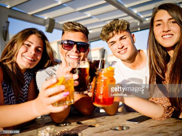 Group of friends with fresh drinks in sidewalk cafe