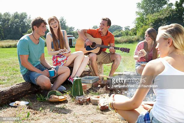 Group of friends with guitar relaxing by campfire
