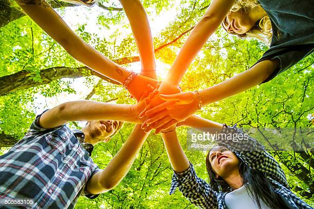 Group of friends with hands in hands - Teamwork