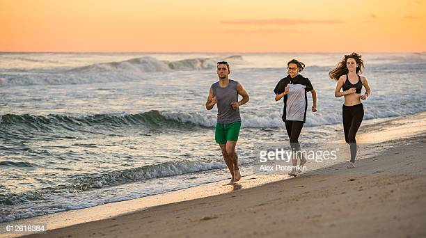 Group of friends, young man and two girls, running beach