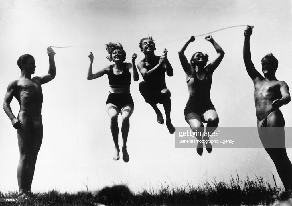 A group of fun-loving teenagers enjoy a game of skipping on the beach.