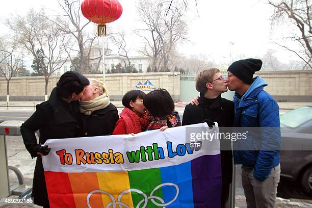 A group of gay and lesbian activists hold a banner of the rainbow flag the Olympic rings and the words 'To Russia with love' as they stage a...