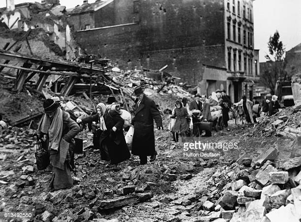 A group of German civilians who had been in air raid shelters for weeks evacuate Aachen to seek safety behind the Allied lines during the Fall of...