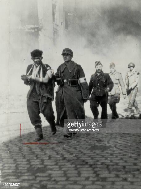 A group of German prisoners including a wounded man left leave the flaming city under guard of a US soldier right The Aachen garrison holds out grimly