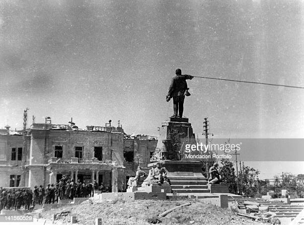 A group of German soldiers throwing themselves against a Lenin statue Sevastopol July 1942