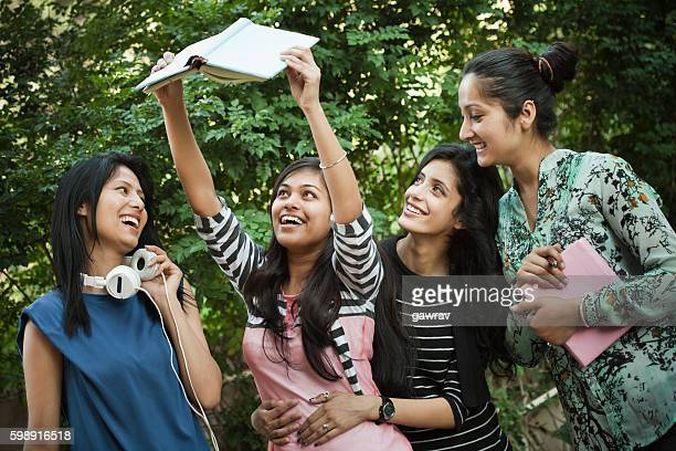 Group of girl students looking at book with toothy smile.