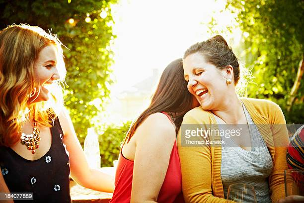 Group of girlfriends sitting on bench laughing