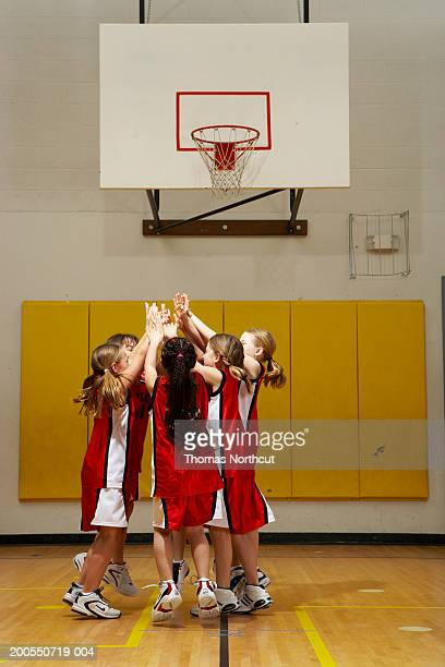 Group of girls (8-10) cheering and high-fiving on basketball court