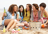 Group Of Girls Enjoying Barbeque On Beach Together