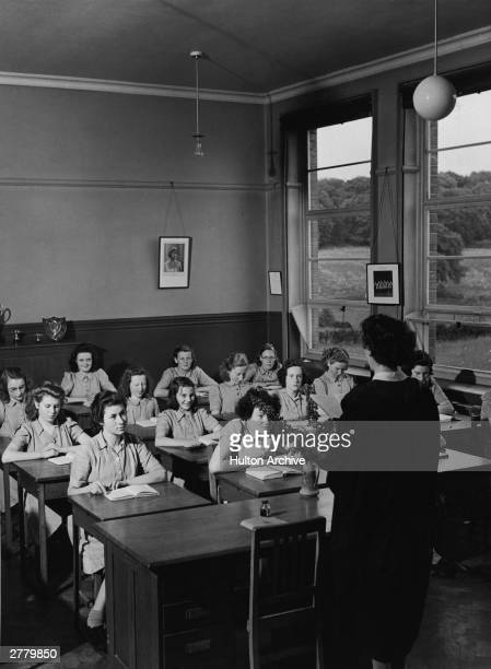 A group of girls from the Dungannon High School sit in a classroom and listen to their teacher read County Tyrone Ireland circa 1950