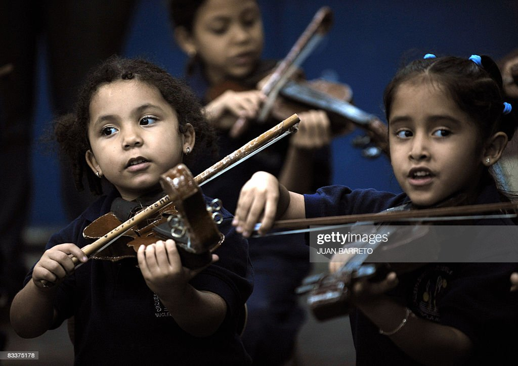 A group of girls hold cardboard violins during a music lesson in a school in La Rinconada neighbourhood in Caracas on October 16, 2008. The National System of Venezuelan Youth and Children's Orchestras (FESNOJIV), which will be awarded the 2008 Principe de Asturias Arts Prize next October 24, was born in this neighbourhood. The so called 'El Sistema', was created by Jose Antonio Abreu in 1975 and has formed more than 750,000 children and youngsters in the course of its 33-year life. AFP PHOTO/Juan Barreto