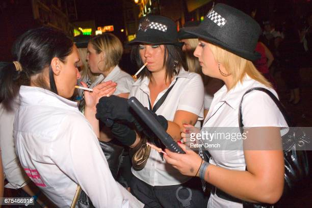 A group of girls on a hen party dressed as police women complete with truncheons hat and handcuffs pause between bars to light cigarettes A...