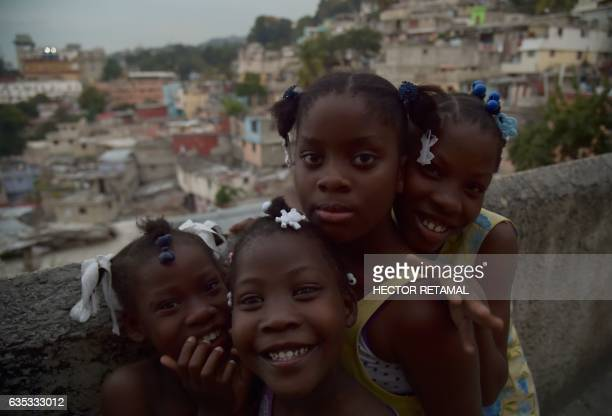 A group of girls pose for a picture in Jalousie neighborhood in the commune of Petion Ville in the Haitian capital PortauPrince on February 14 2017 /...