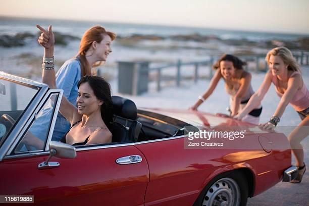 Group of girls pushing a broken car