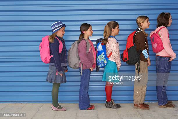 Group of girls (8-11) queuing along wall, side view