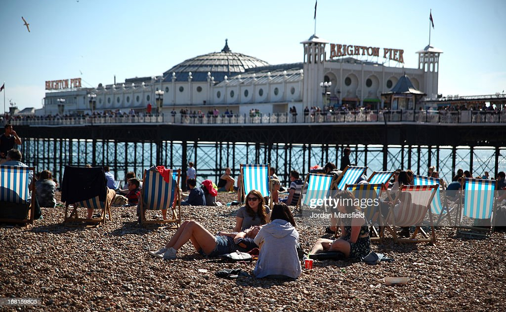 A group of girls relax on the beach in front of Brighton Pier on May 6, 2013 in Brighton, England. Visitors have flocked to Brighton Beach as the Met Office predicted the May Day Bank Holiday to be the hottest day of the year so far.