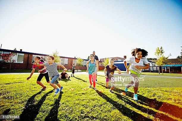 Group of girls running race during athletics class