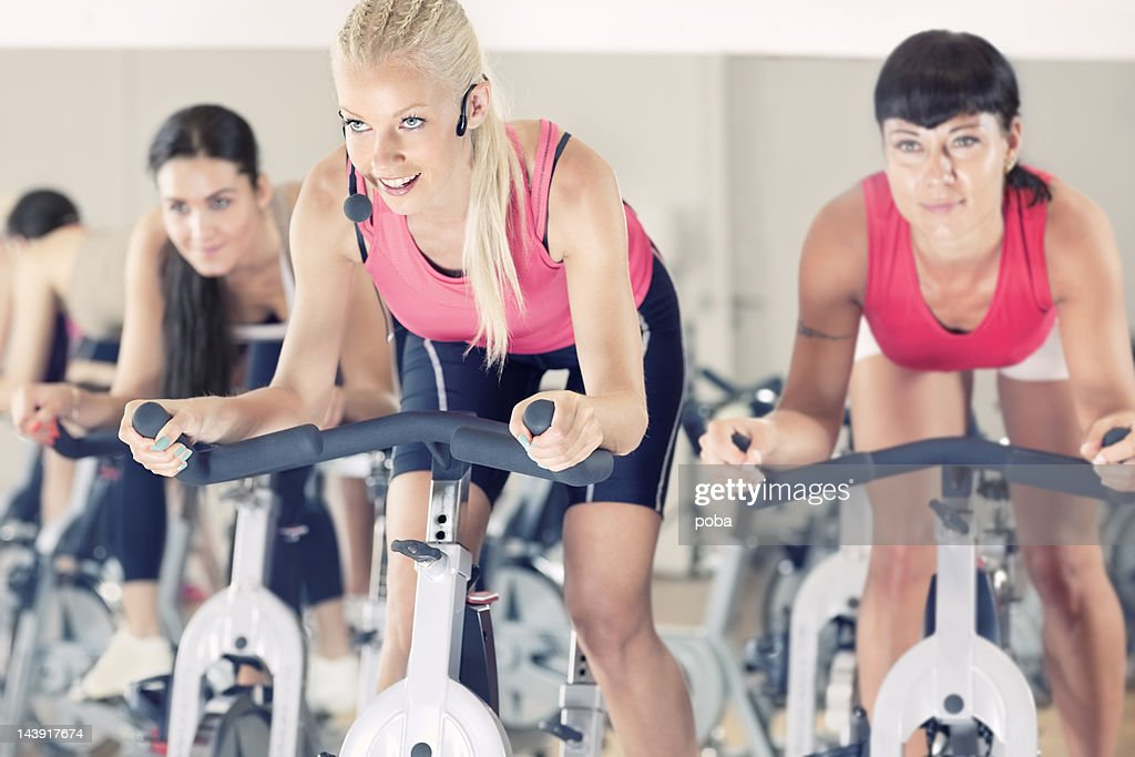 group of  girls spinning on bicycles in  gym. : Stock Photo