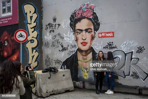 A group of girls take photographs in front of street art showing artist Frida Kahlo on February 22 2017 in Istanbul Turkey Turkey will hold its...