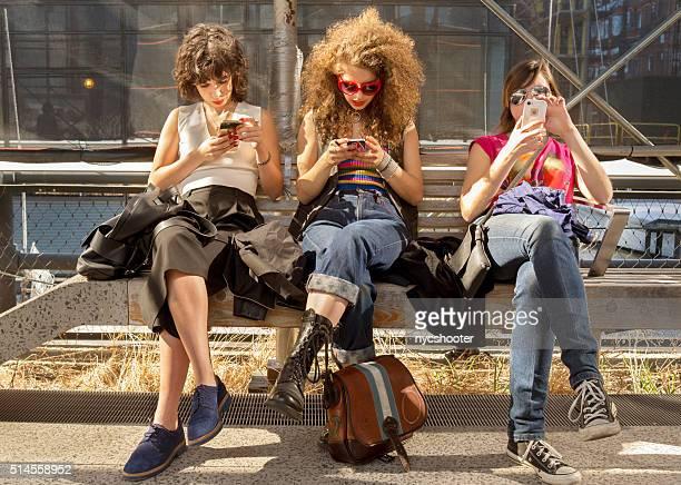 Eine Gruppe von Mädchen SMS auf Smartphones in NYC