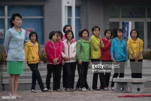 A group of girls watch as a propaganda troupe perform a flagwaving routine outside the central railway station in Pyongyang on September 27 2017 /...