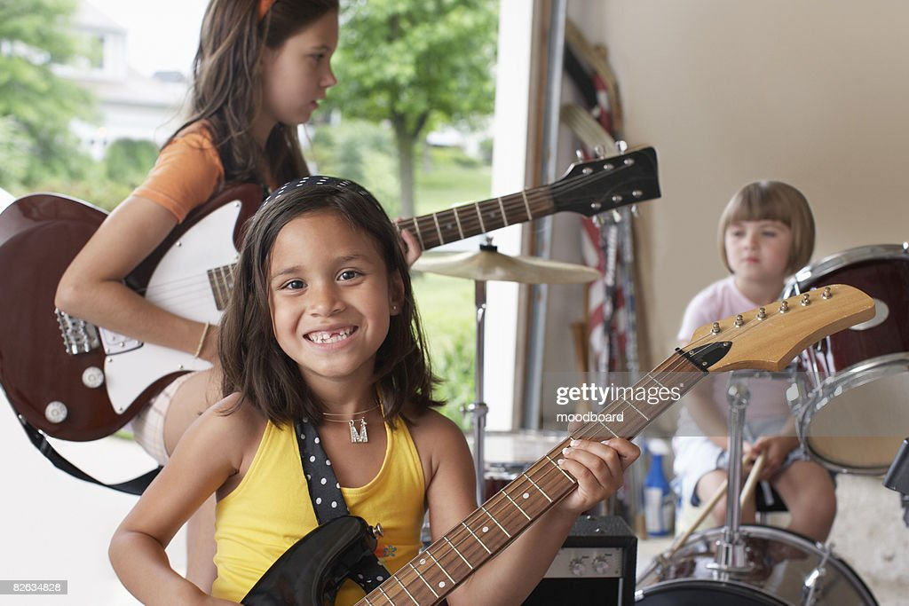 Group of girls (7-9) with instruments in garage : Stock Photo