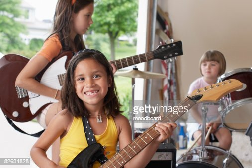 Group of girls (7-9) with instruments in garage : Foto de stock