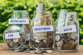 group of glass jar bottles with full of coins and banknotes labeled as investment, house, car and retirement as savings or investment concept.