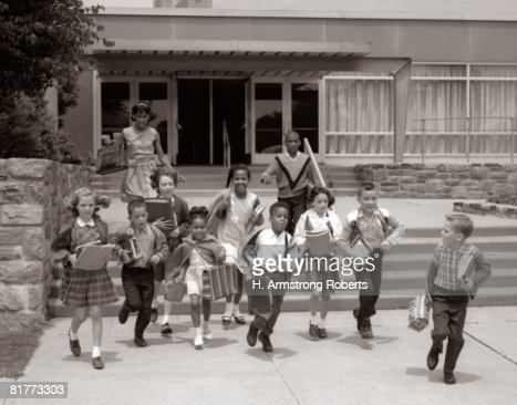 Group Of Grade School Children Running Down School Stairs With Books & Bags. : Stock Photo