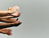 A groups of hands are held out, clapping enthusiastically against a gray background.